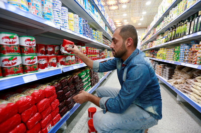 © Reuters. A shop worker arranges the cans of Iranian tomato paste at a super market in the city of Najaf