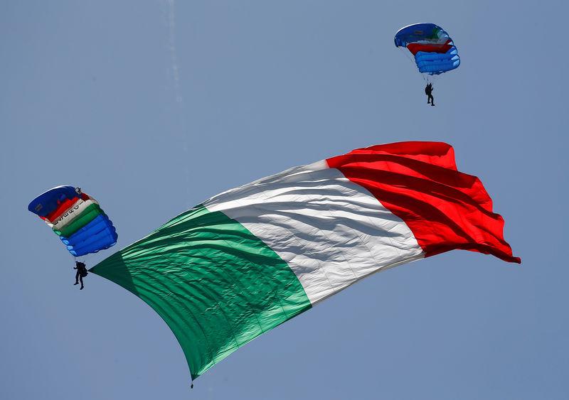© Reuters. FILE PHOTO: Italian Army parachutists hoist an Italian flag during a military parade in Rome