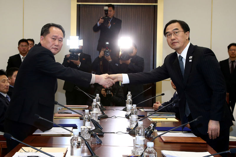 © Reuters. FILE PHOTO: Head of the North Korean delegation, Ri Son Gwon shakes hands with South Korean counterpart Cho Myoung-gyon as they exchange documents after their meeting at the truce village of Panmunjom