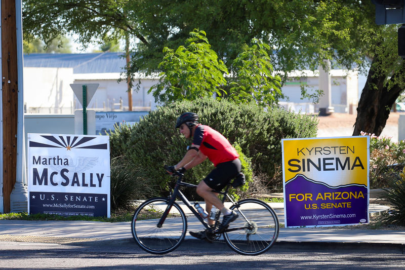 © Reuters. FILE PHOTO: A man rides a bicycle past campaign signs for Arizona U.S. senatorial candidates Krysten Sinema and Martha McSally following the U.S. Midterm elections in Scottsdale, Arizona