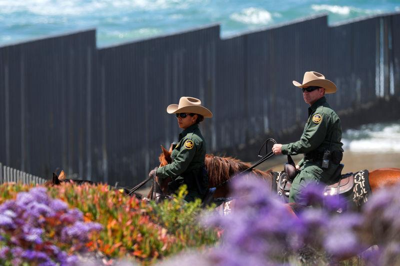 © Reuters. U.S. border patrol agents ride past the U.S.-Mexico border wall on horseback near San Diego