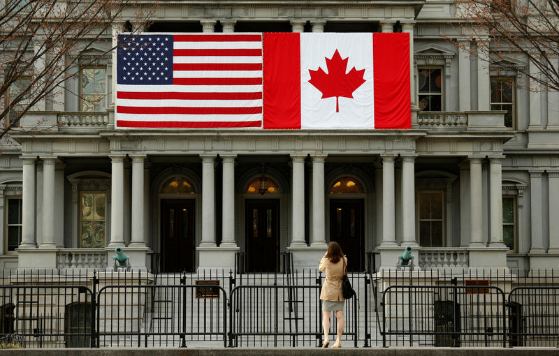 © Reuters. FILE PHOTO: A woman stops to take a photo of the U.S. and Canadian flags placed side-by-side on the Eisenhower Executive Office Building next to the White House in Washington