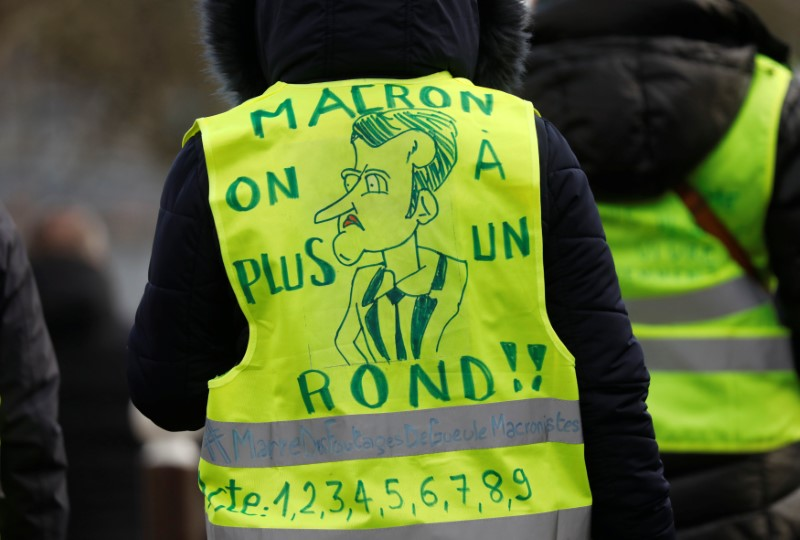© Reuters. A protester wearing a yellow vest attends a demonstration with French unions against the French government policies in front of the sport hall