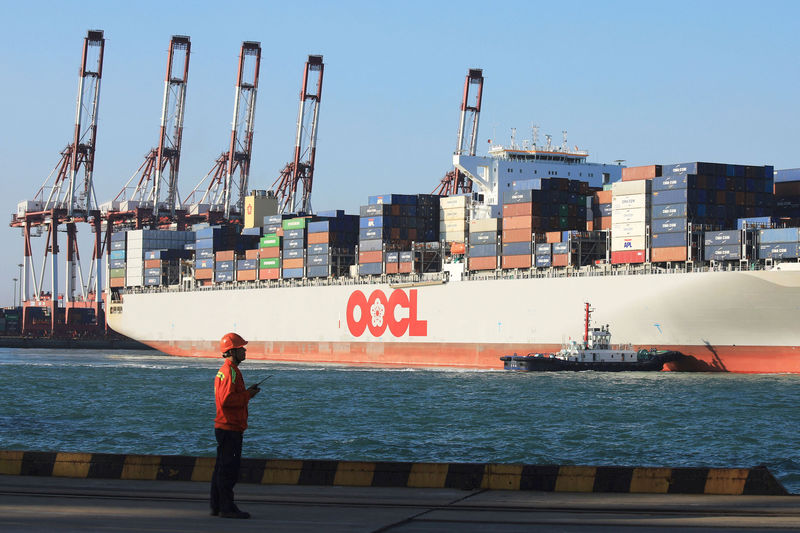 © Reuters. Worker stands in front of an OOCL container ship at a port in Qingdao