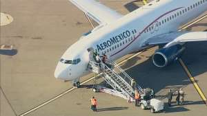 a person standing in front of a plane: An Aeromexico plane headed for San Francisco International Airport from Guadalajara was diverted due to fog to Oakland International Airport Thursday afternoon, officials said.