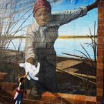Photo of 3-year-old girl reaching out to Harriet Tubman mural goes viral