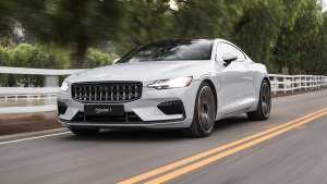 a car driving on a road: 2020 Polestar 1 front three quarter in motion 1